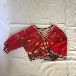 Flowery reddish-orange blouse.
